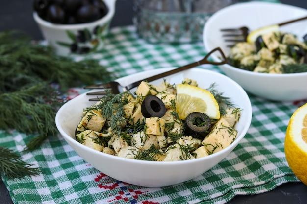 テーブルの上の白いボウルにチキン、チーズ、ブラックオリーブのサラダ