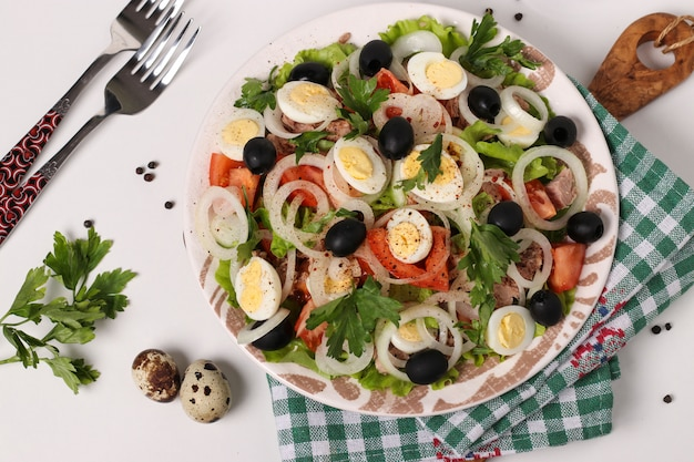 缶詰マグロ、トマト、ウズラの卵、ブラックオリーブ、白玉ねぎの有機レタスのヘルシーサラダ