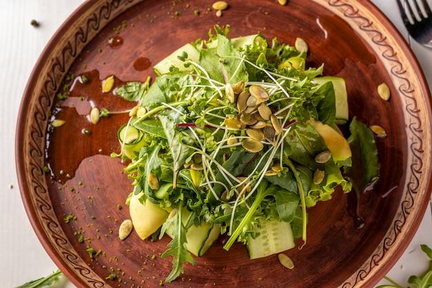 オリーブオイルで味付けしたアボカド、キュウリ、ルッコラ、マイクログリーンを使ったベジタリアンに役立つグリーンサラダ