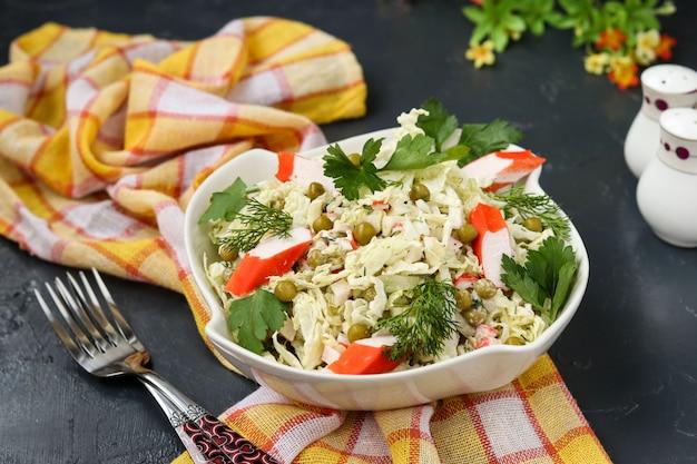 Полезный салат с китайской капустой, консервированным горошком и крабовыми палочками в миске