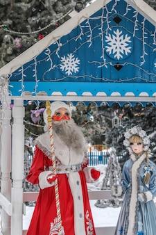 新年の休日に子供と大人のためのレクリエーションエリアである屋外公園の新年のアーバーでのスネグーラチカとサンタクロースの姿
