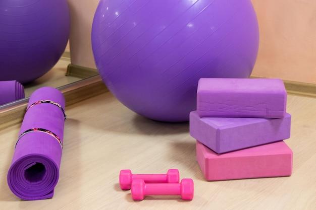 Фитнес-инструменты - шарики, розовые и фиолетовые кубики и гантели