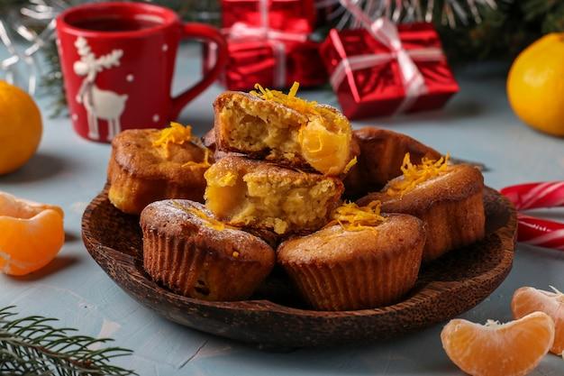 Домашние кексы с мандаринами, посыпанные сахарной пудрой на новый год или рождество светло-голубые