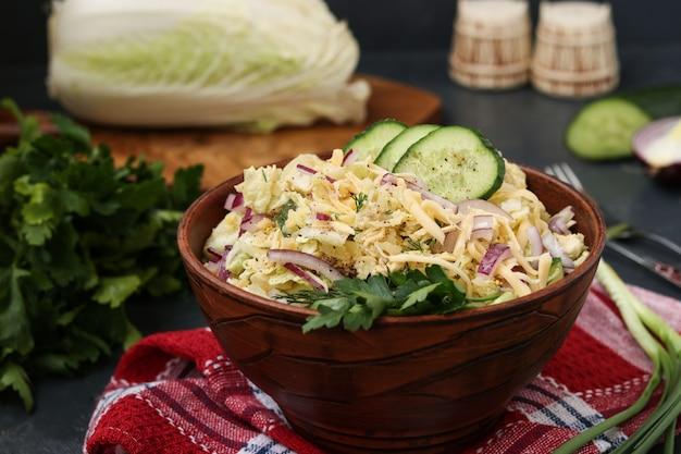 Салат из пекинской капусты, огурца, красного лука и сыра в миске