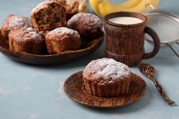 Банановые маффины с овсяными хлопьями, посыпанные сахарной пудрой на кокосовую тарелку и стакан молока, горизонтальная ориентация