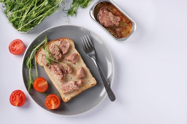Здоровая еда, бутерброд с печенью трески, гороховые микрогрины и помидоры черри на серой тарелке на белом фоне