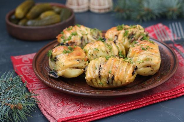 Запеченная картошка-гармошка с грибами и сыром расположена в тарелке на темном фоне