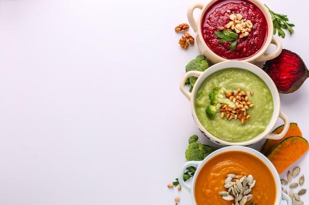 様々なカラフルな野菜のクリームスープ:ブロッコリー、ビート、カボチャ、健康的な食事のコンセプト、コピースペース、水平方向