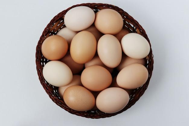 Сырые куриные яйца в плетеной корзине на белой поверхности
