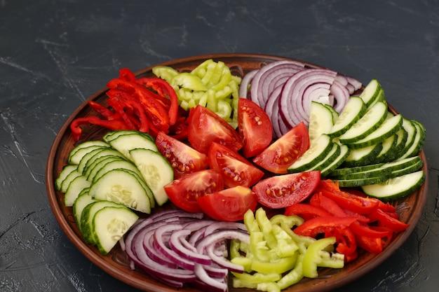 Полезный салат из помидоров, красного лука, перца и огурцов расположен на тарелке на темной поверхности. вид сверху