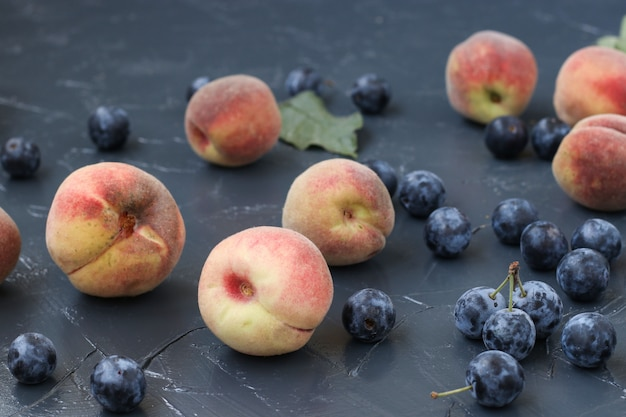 Персики и терновник расположены на темной поверхности