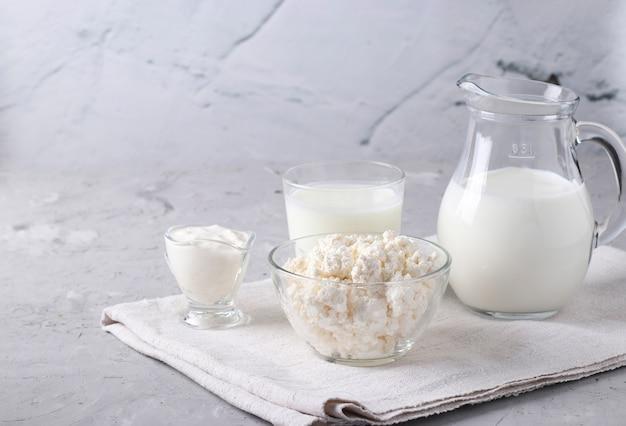 Молочные продукты: молоко, кефир или айран, творог и сметана в прозрачной миске, кувшин и стакан на серой поверхности, место для текста, крупным планом