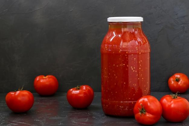 暗い壁のテーブルに置かれた瓶の中のトマトジュース