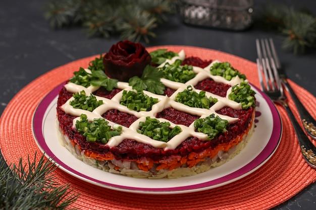 Традиционный русский праздничный салат из сельди под шубой на новогоднем украшении