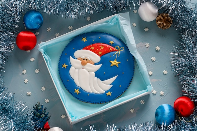 青いテーブルのジンジャーブレッドサンタクロース、ギフトクリスマスやノエルの休日、水平方向