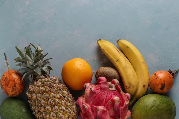新鮮なトロピカルフルーツ:マンゴー、パイナップル、ドラゴン、キウイ、バナナ、オレンジ、パッションフルーツ