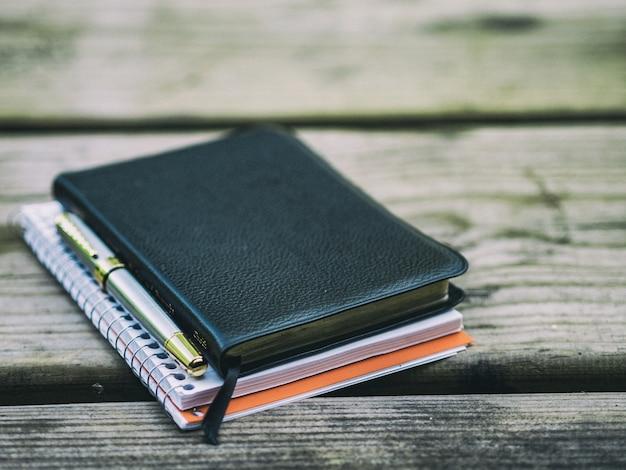 Блокноты и кожаный дневник на старой деревянной скамейке