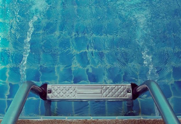 青いプールのはしごをつかむ。