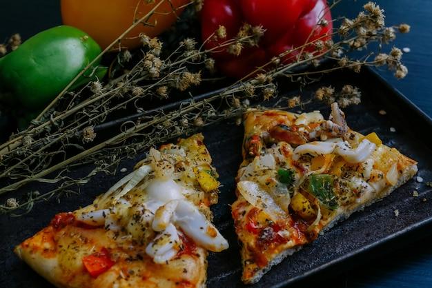 テーブルの上のトマトとコショウのイタリアのピザ