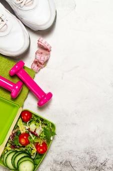 緑色のタオルと巻尺とピンクの重み