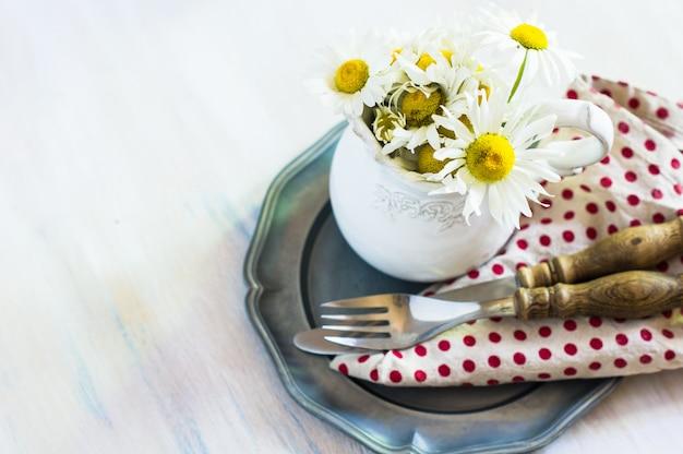 Весенний интерьерный стол с цветами и столовыми приборами