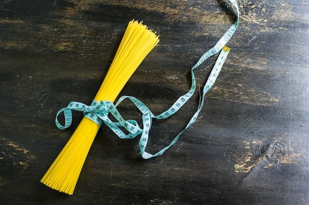Спагетти и мера ленты ом деревянный фон как концепция потери веса