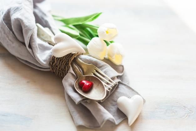 День святого валентина с сервировкой стола, цветами и сердцами