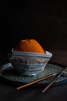 Концепция здравоохранения с минималистичным столом с оранжевыми фруктами в маске