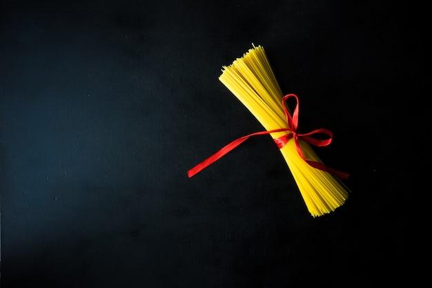 食品背景概念として黒の背景に薄い長いスパゲッティ。