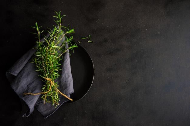 暗い木製のテーブルにローズマリースパイス