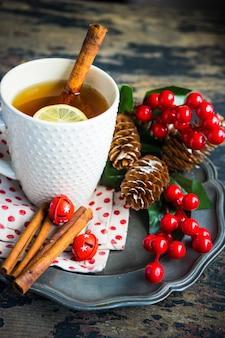 Чашка чая с лимоном и рождественские украшения
