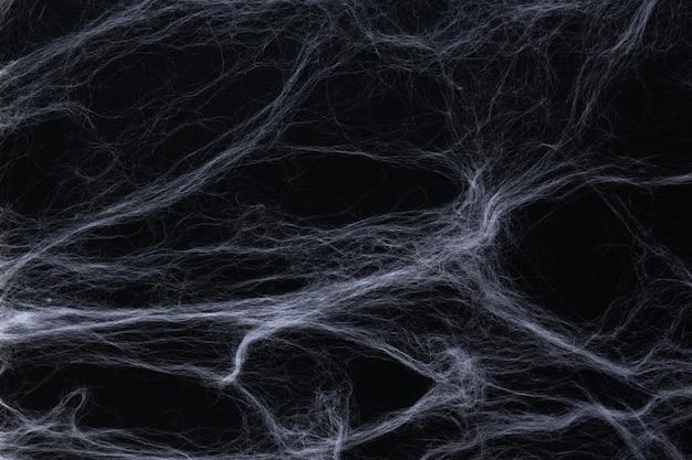 ハロウィーンのコンセプト。黒の背景に抽象的なクモの巣。