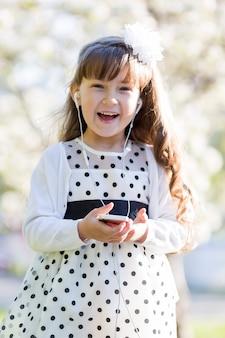 女の子は携帯電話から音楽を聴きます。