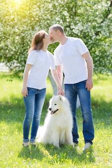 Влюбленные люди гуляют с собакой в деревне.