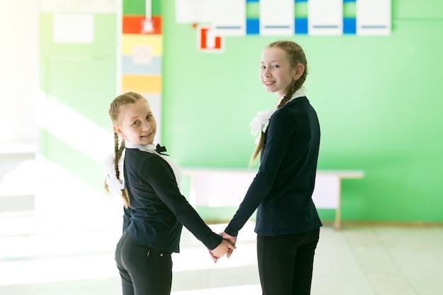 女子高生の女の子は手をつないで行きます。
