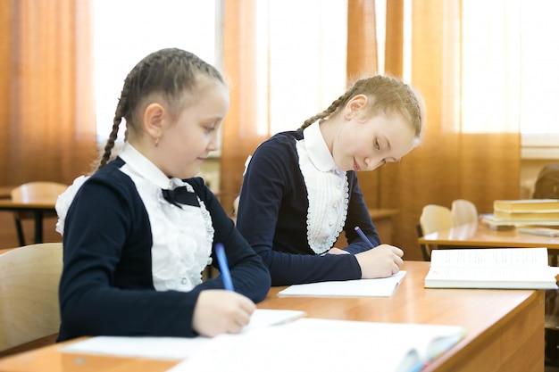 Девочка одноклассника заглядывает в чужую тетрадь.