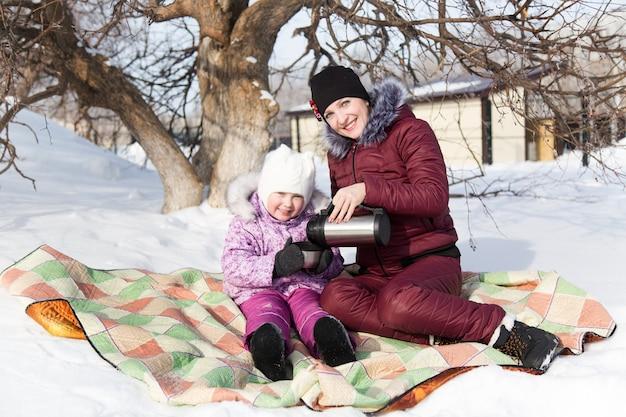 ママと娘はピクニックで魔法瓶からお茶を飲みます。