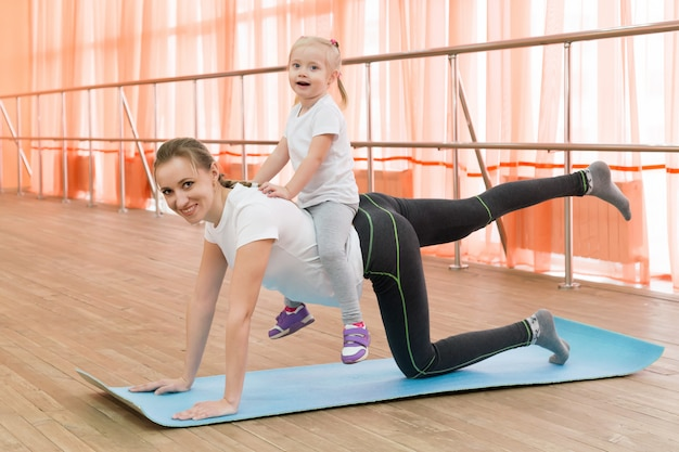 Женщина занимается спортом с ребенком на спине.