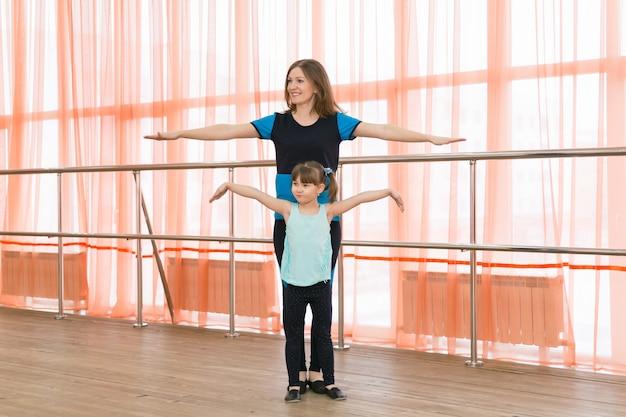 Маленькая девочка и ее мать занимаются спортом.