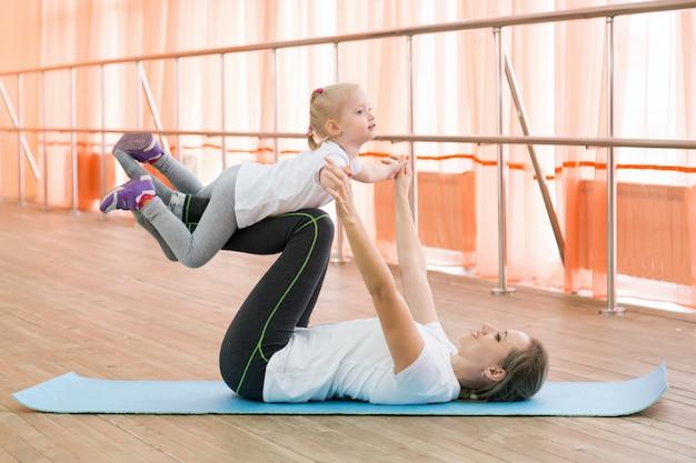 女性は少女の足を持ち上げるスポーツに従事しています。