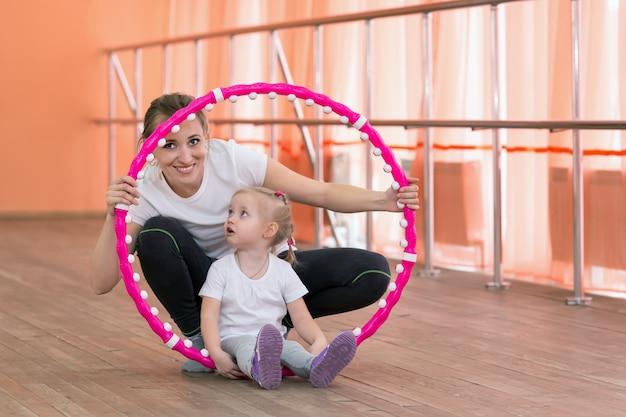 Мама и дочка занимаются спортом с обручем.