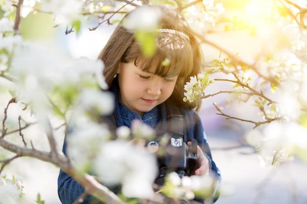 Красивая маленькая девочка держит камеру в руках.