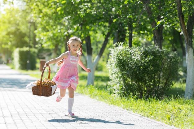 女の子はパンのバスケットを持って道を走っています。