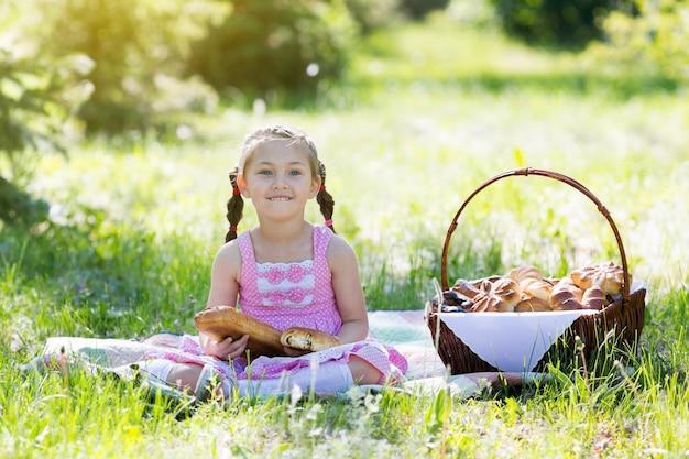子供が草の上に座ってパンを食べています。