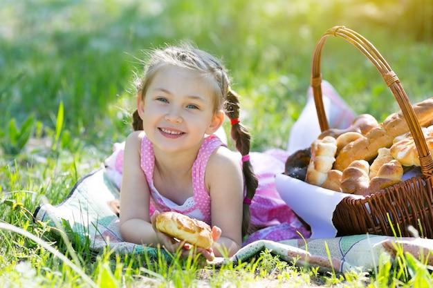 Ребенок ест хлеб, сидя на траве.