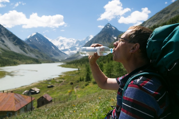 Мужчина пьет воду из бутылки на фоне гор.
