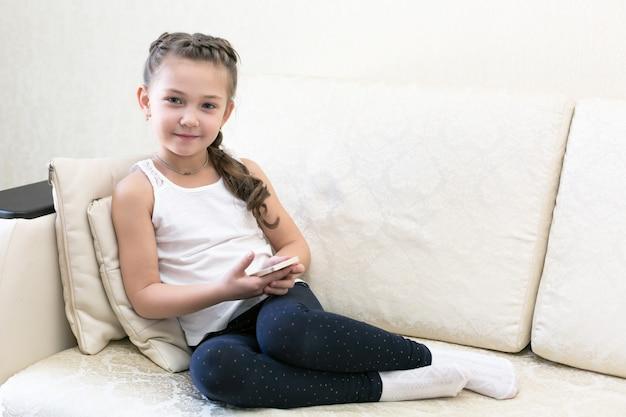 ソファの上の携帯電話を持つ少女。