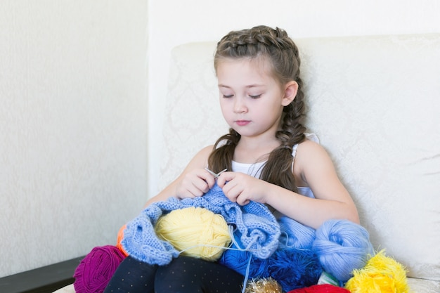 Девушка вяжет с вязанием и ниткой.