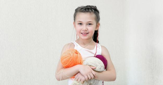 編み物用の糸のボールを持つ少女。