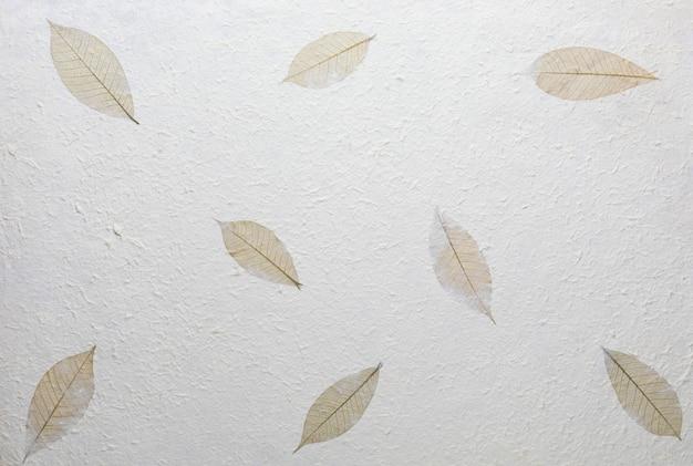 リサイクル素材、木の葉、綿繊維を使用した手作りの紙のテクスチャ。